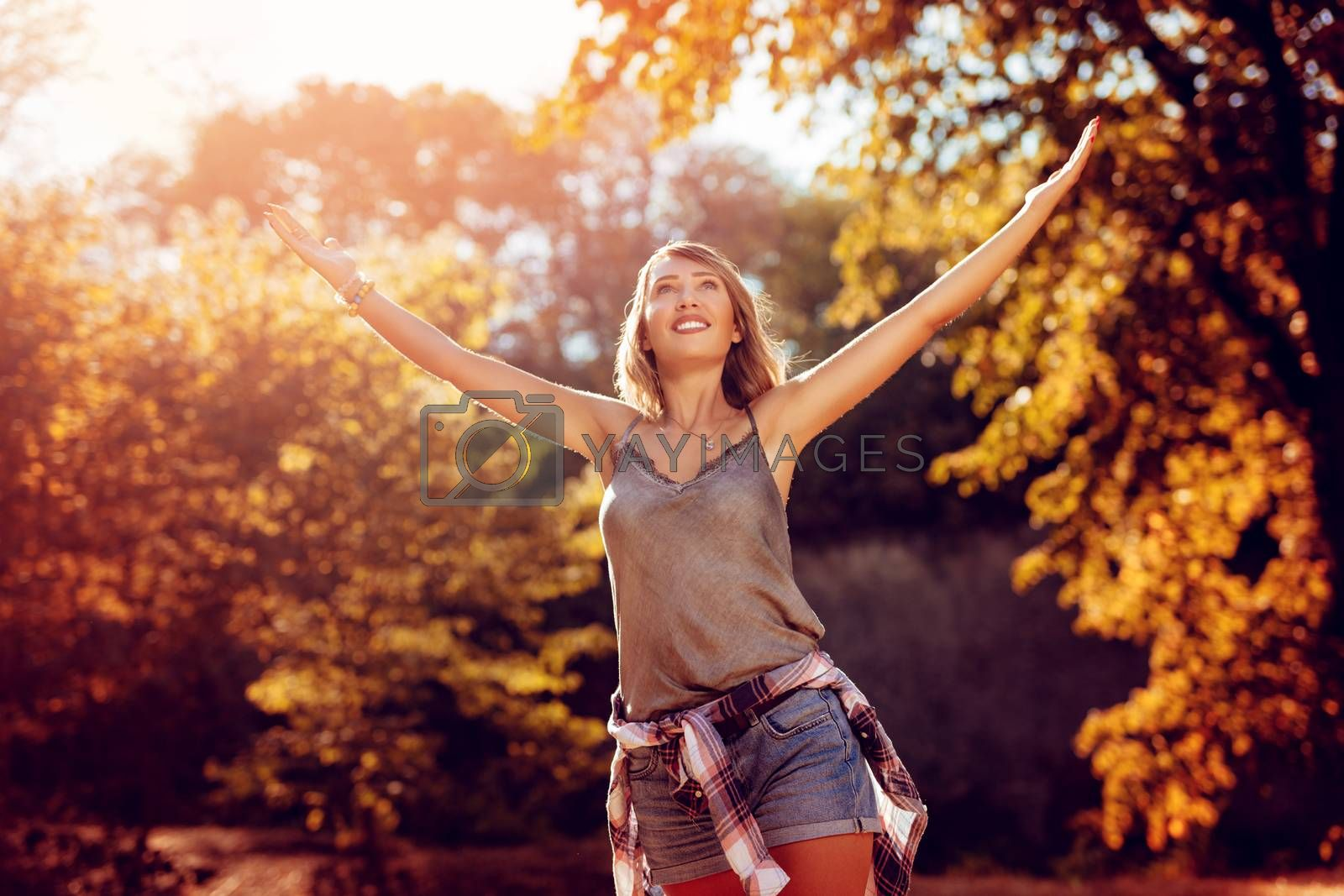 Happy young woman with open arms enjoying in the nature in autumn.