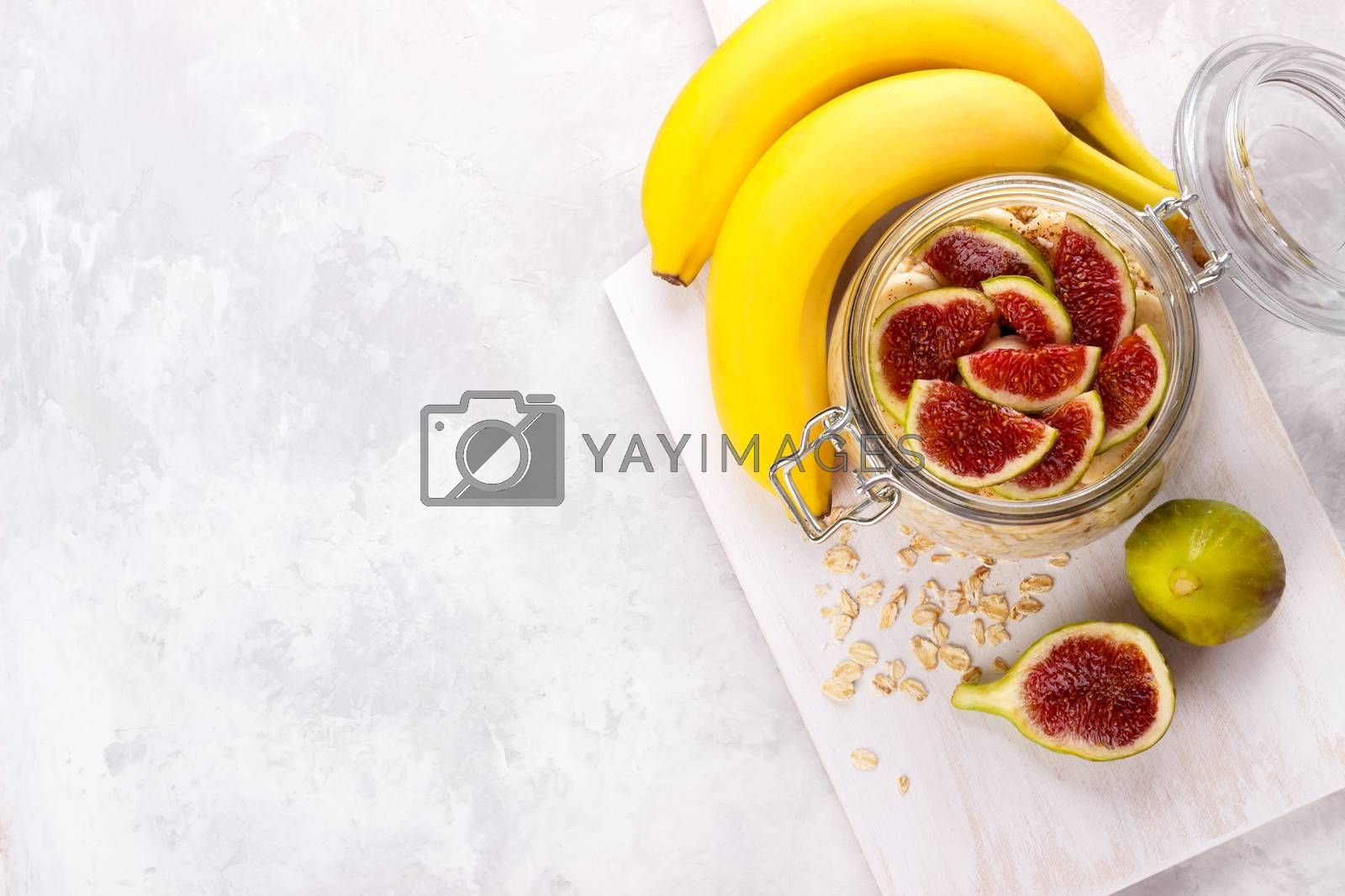 Old fashion oats with greek yogurt , banana and figs in a jar on white rustic background
