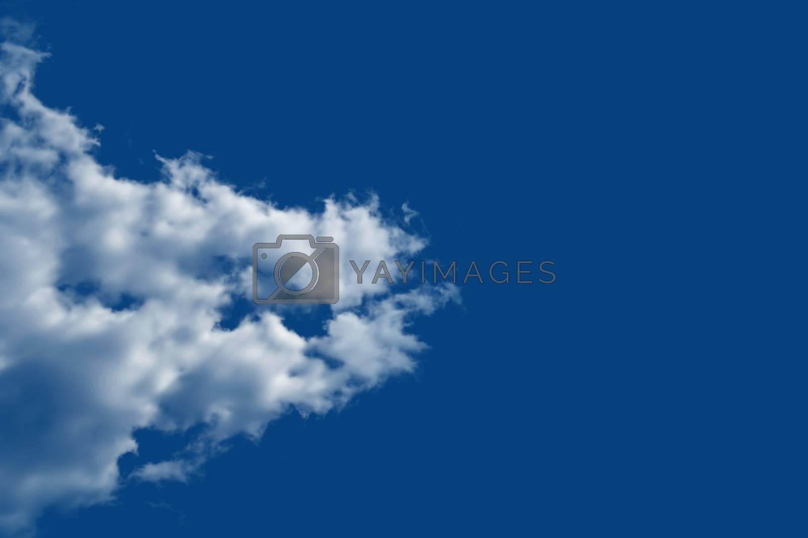 A bright white cloud in clear, bright deep blue summer sky