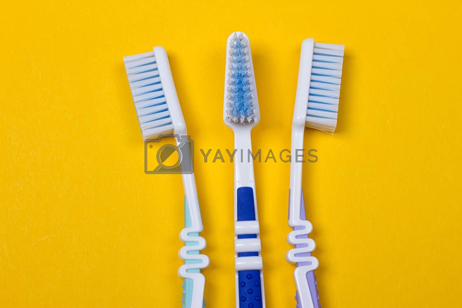 three Toothbrushes on the yellow background. Top view