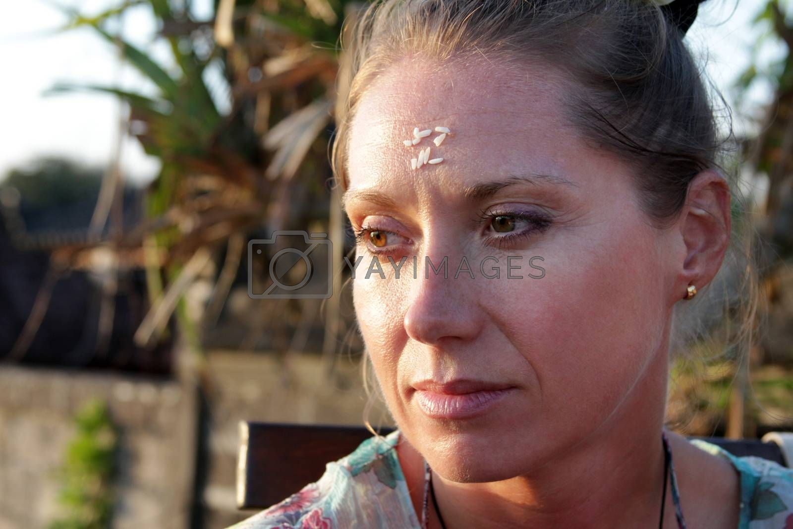 Portrait of a woman with rice on her forehead. Rice on the forehead after the end of prayer is a symbol of longevity, prosperity and closeness to God