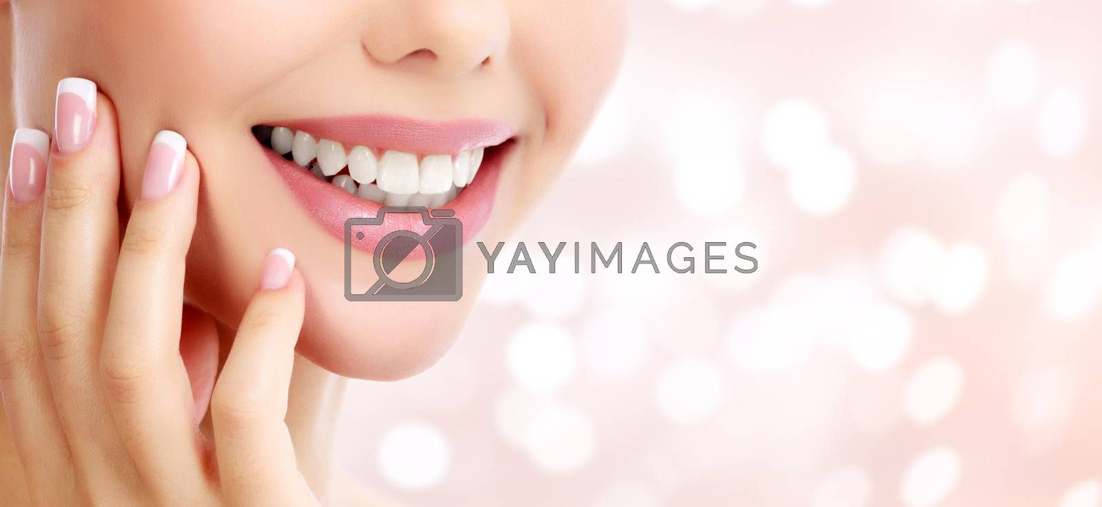 Closeup shot of beautiful female smile, abstract background with blurred lights
