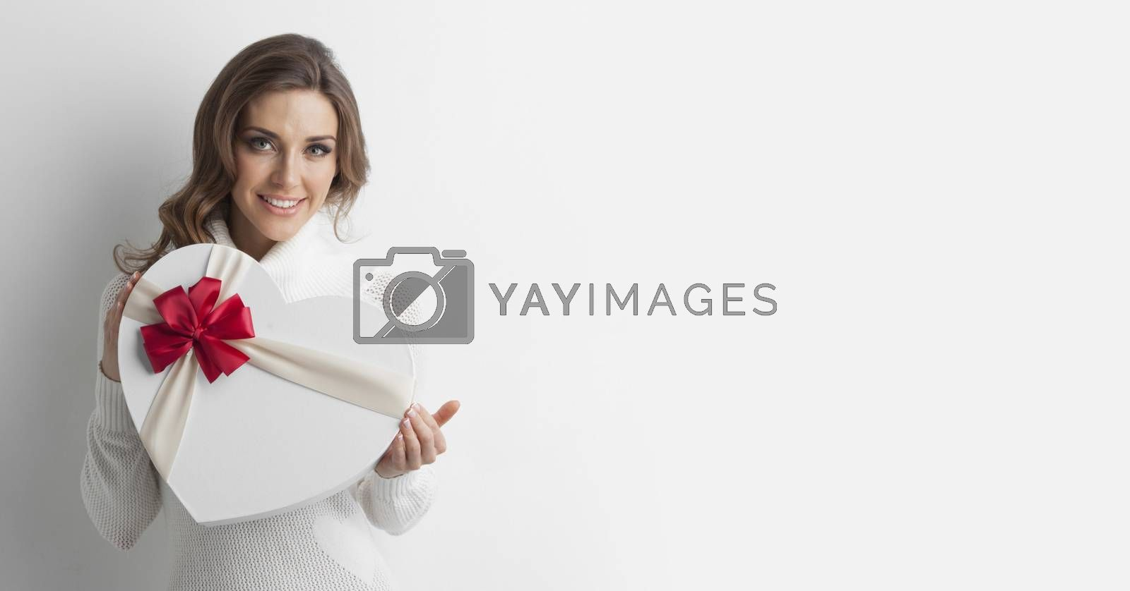 Young girl with heart-shaped gift box on white background