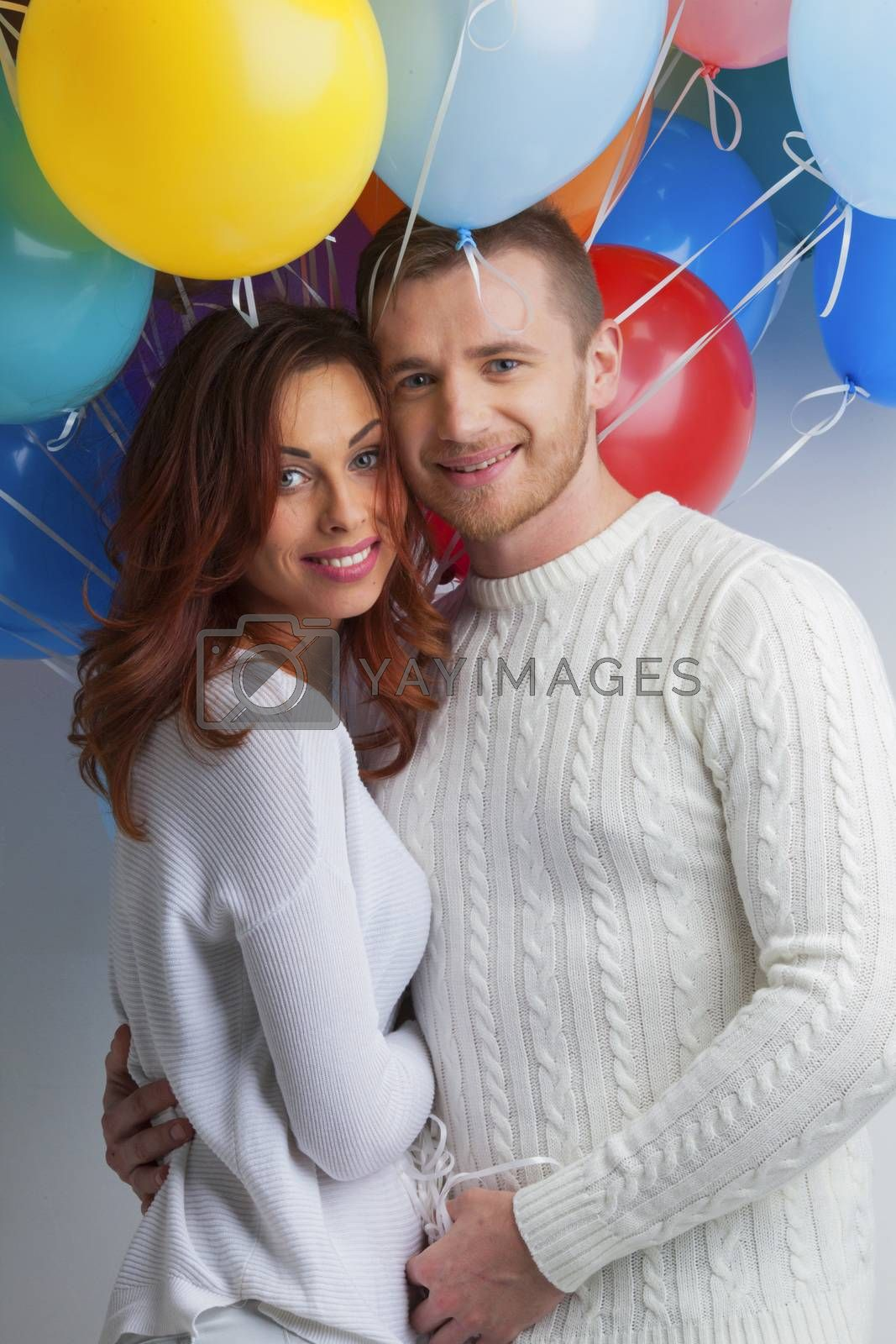 Young smiling hugging couple with balloons