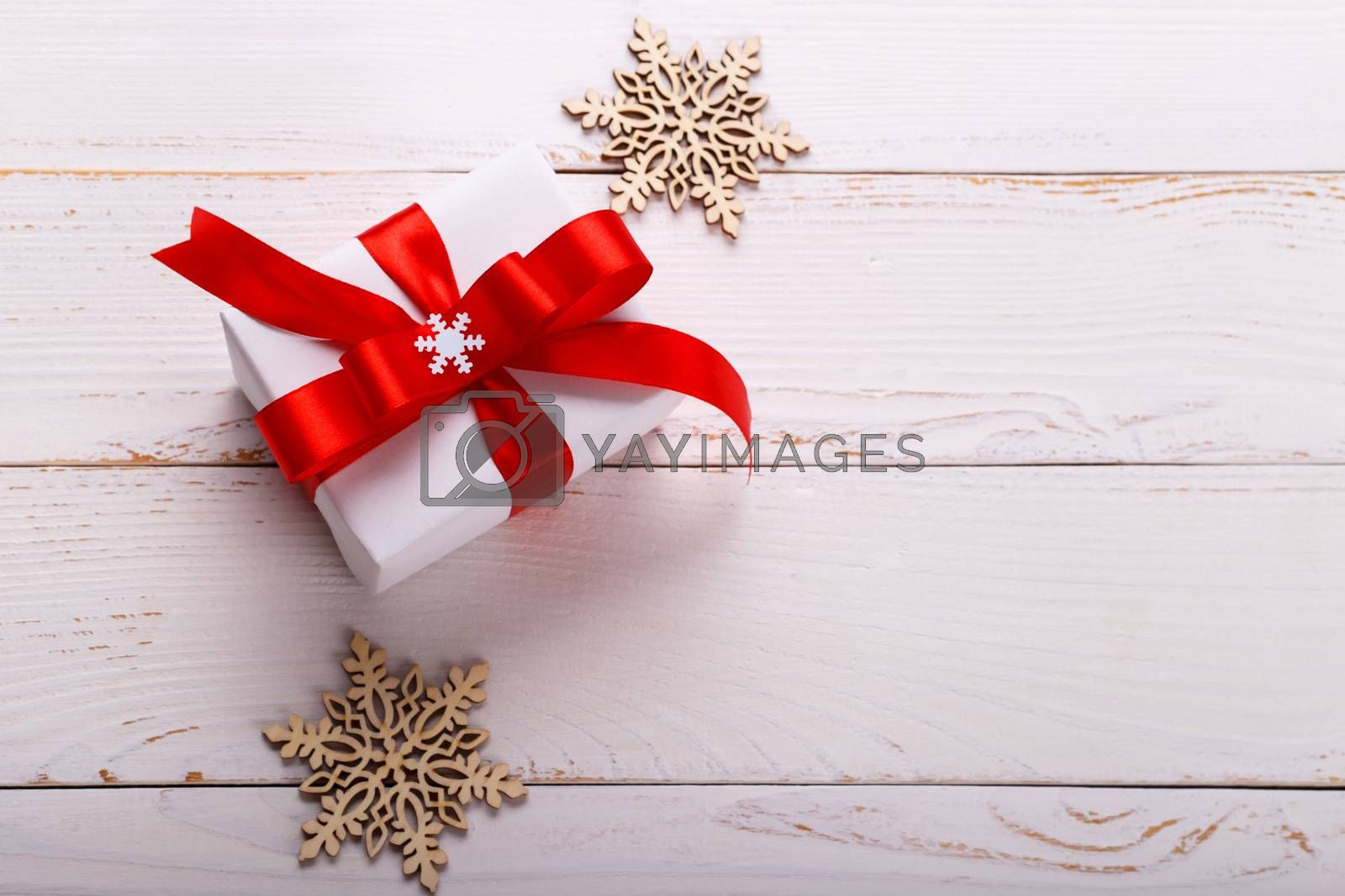 Christmas white gift box with red ribbon rustic wooden background.Scandinavian style selective focus