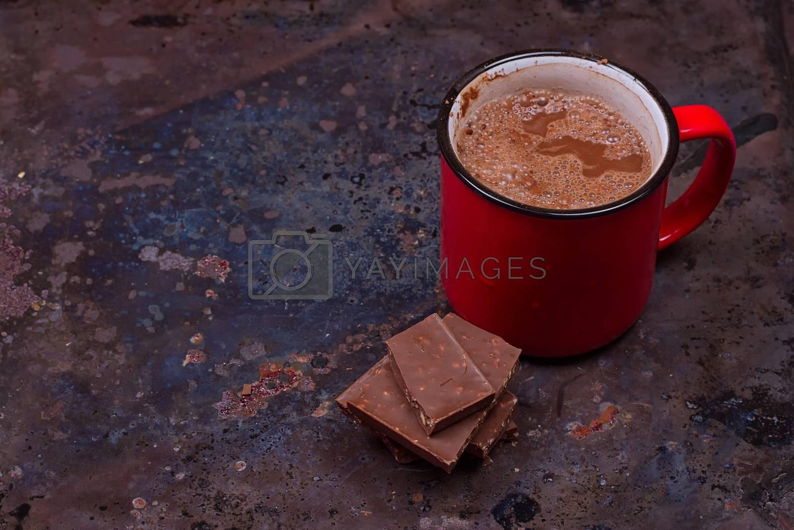 Hot chocolate in mug with chocolate on grunge dark table