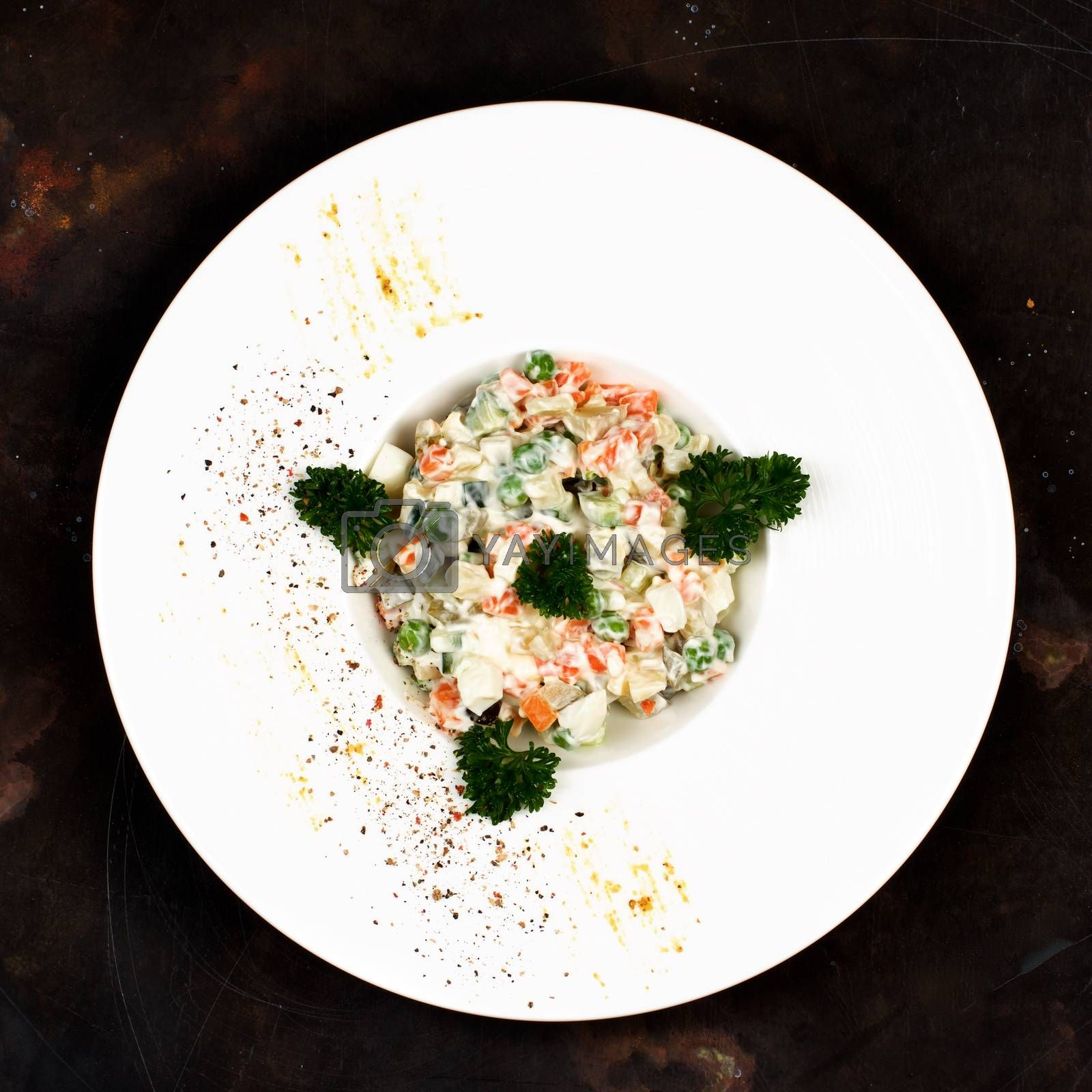 Traditional Russian Salad Olivier with Boiled Chicken Meat, Eggs and Vegetables Decorated with Parsley in White Plate on Dark background. Top View