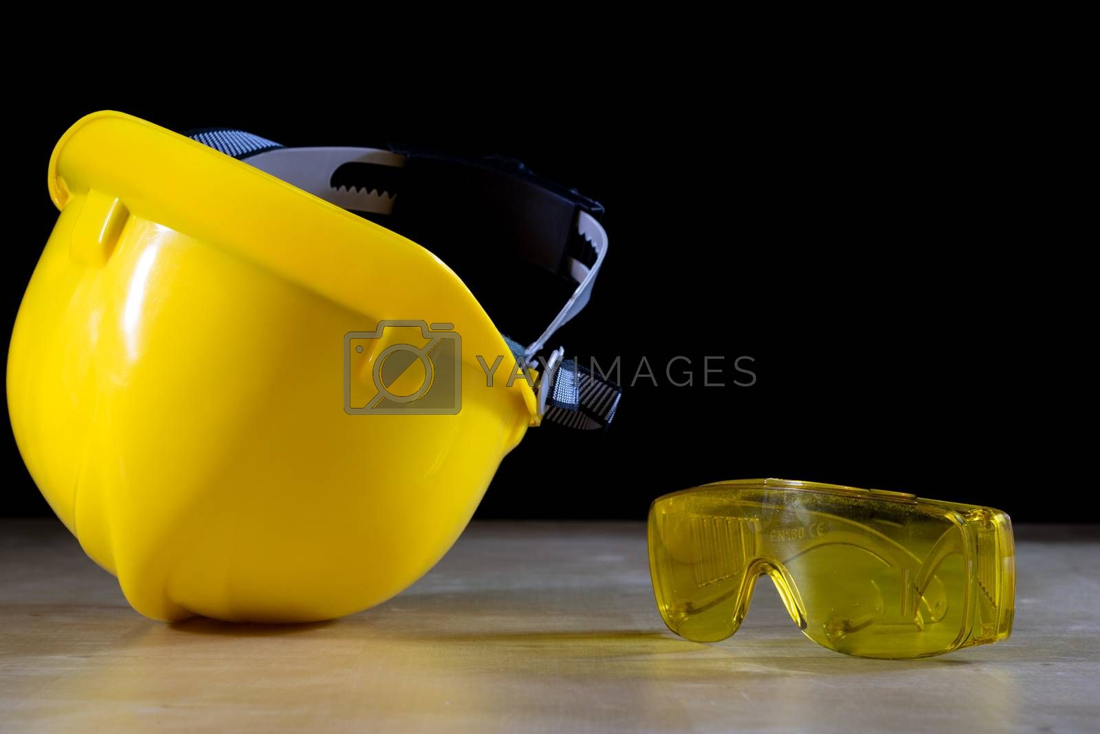 Yellow helmet, safety goggles and work gloves for the worker, black background