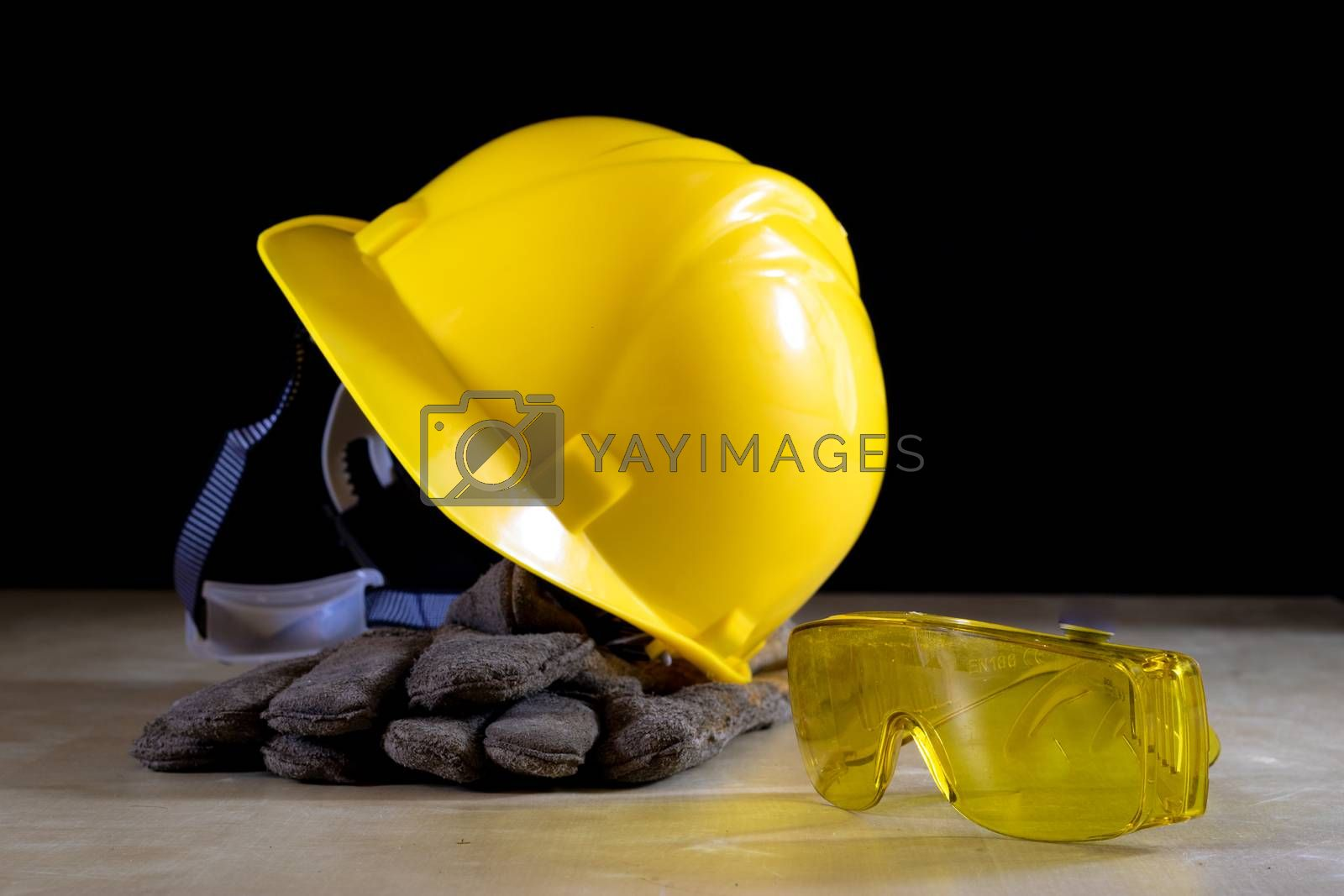Yellow helmet, safety goggles and work gloves for the worker on  by wytrazek