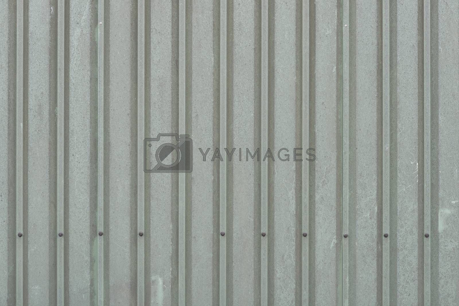 Background of weathered dark green metal wall panels on a barn