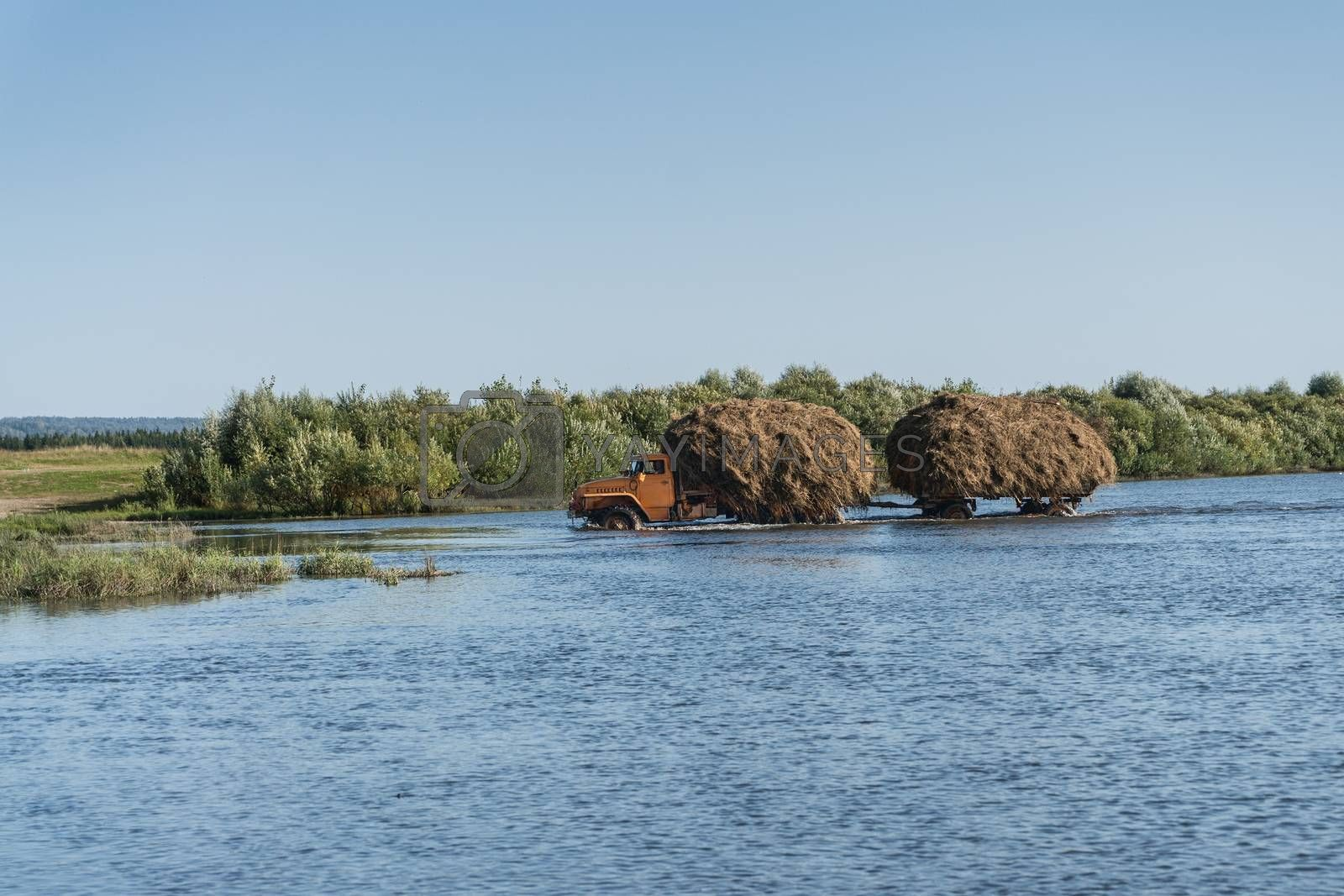 A truck with a trailer carries hay through the river
