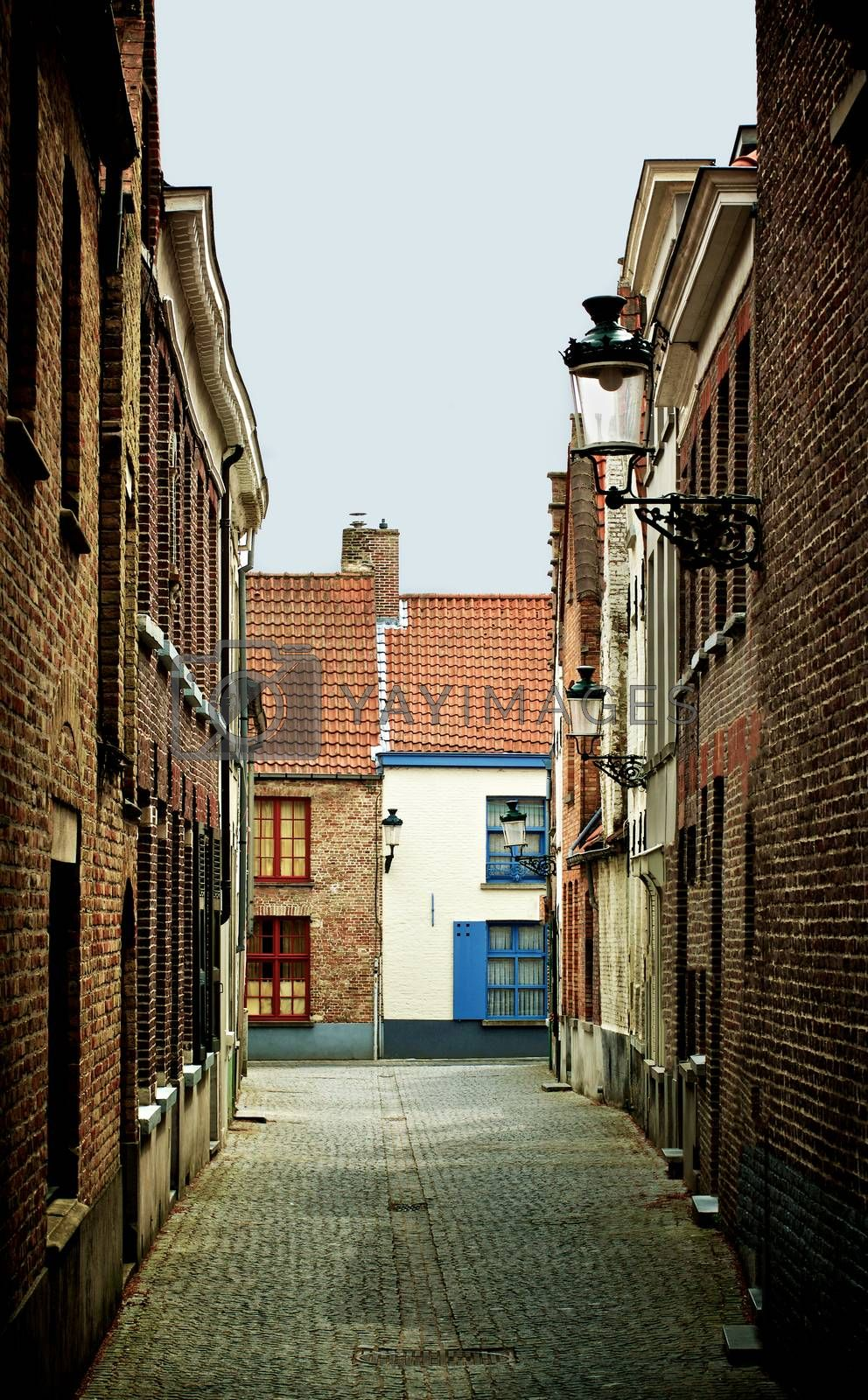 Obsolete Narrow Street with Multi Colored Old Houses and Street Lantern in Cloudy Day Outdoors. Bruges, Belgium
