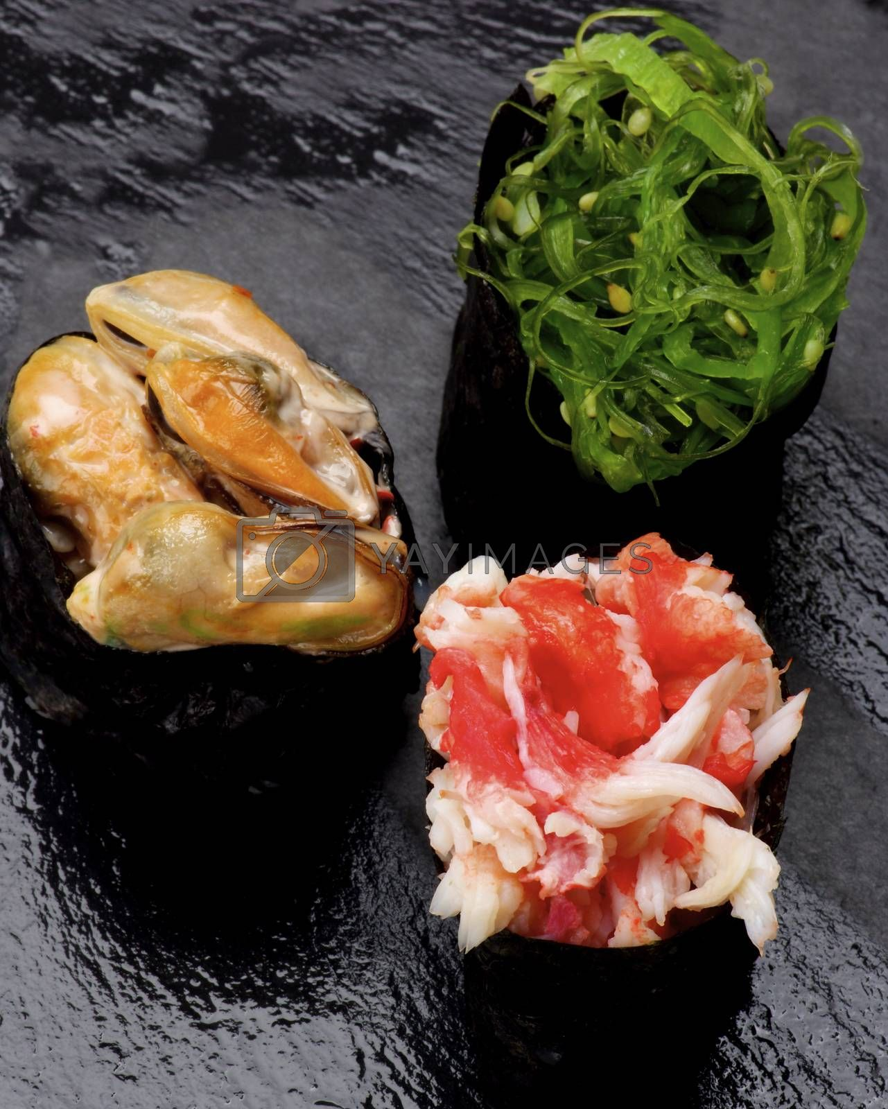 Various Japanese Sushi Gunkan Rolled Up in Nigiri with Seaweed, Shrimps and Mussels in Sauce closeup on Wet Slate background. Focus on Foreground