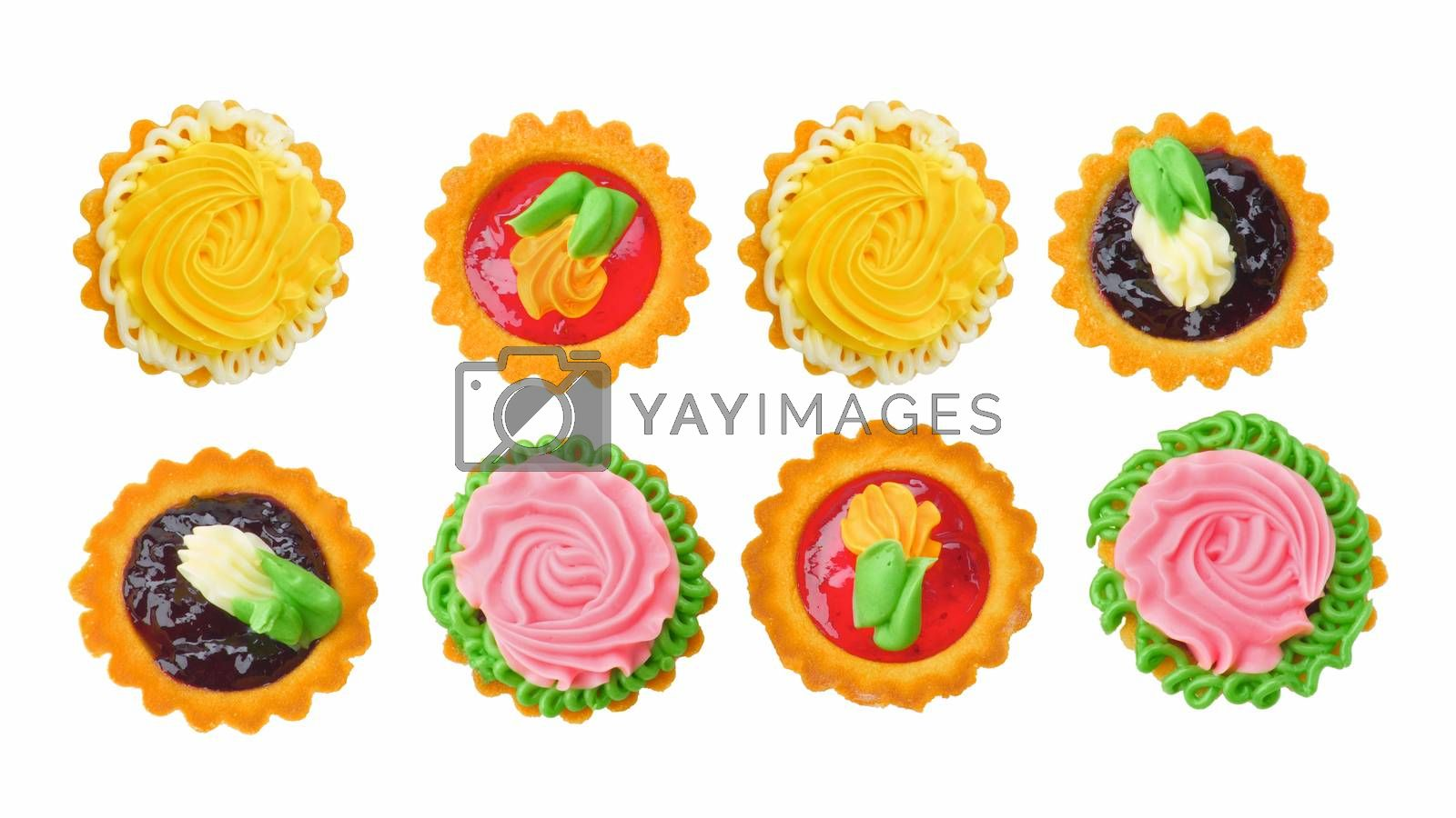 Two Rows of Delicious Little Tarts with Colored Butter Cream, Fruit Jam and Decoration isolated on White background. Top View