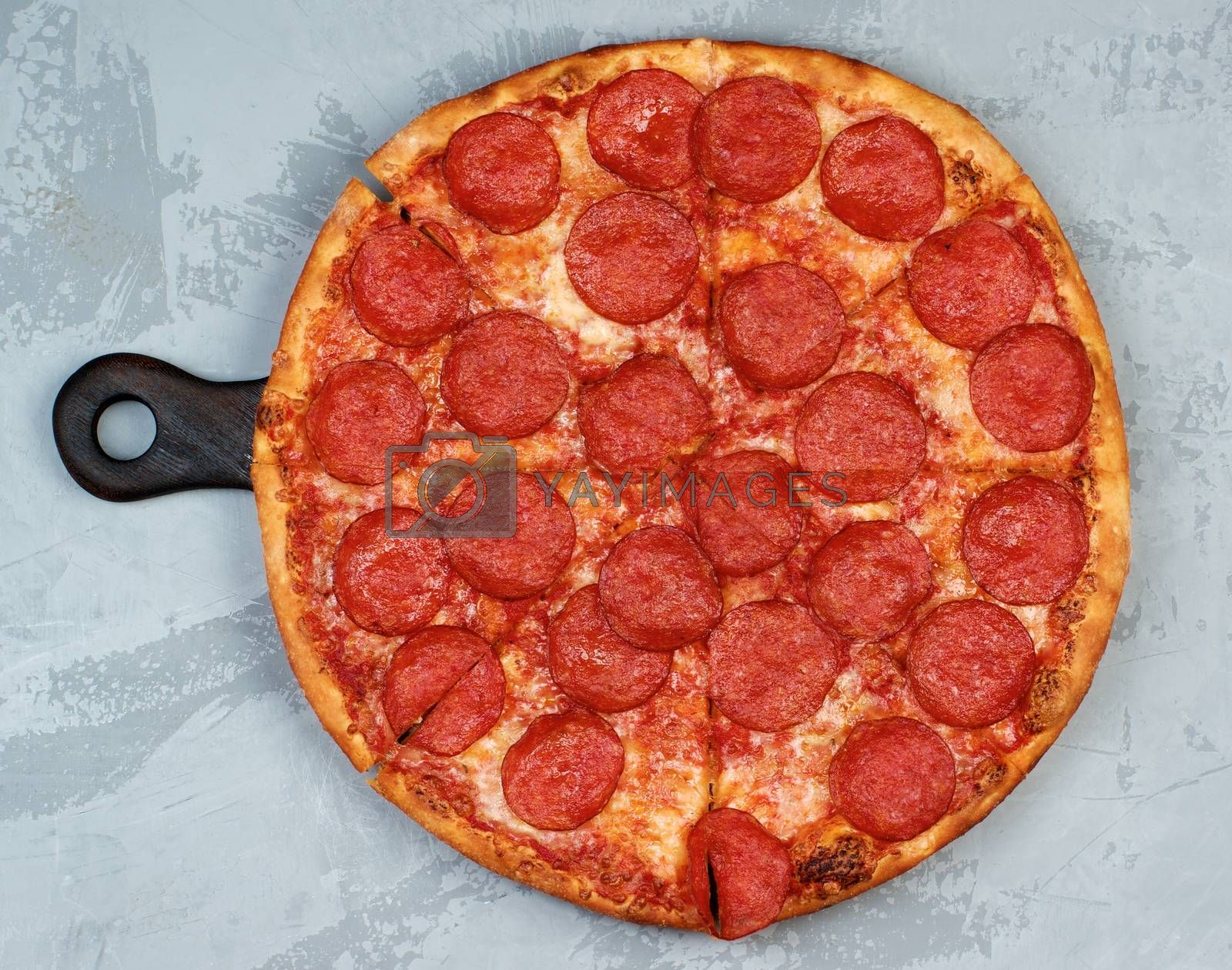 Freshly Baked Pepperoni Pizza with Tomato Sauce, Pepperoni and Cheese on Cutting Board on Grey Textured background. Top View