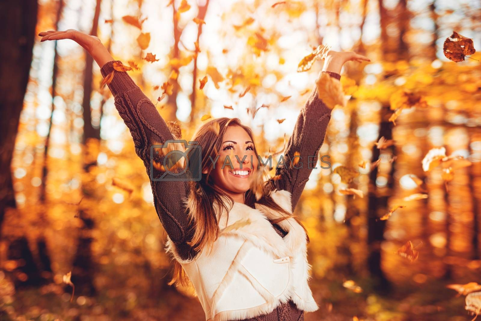 Cheerful young woman having fun in sunny forest in autumn colors.