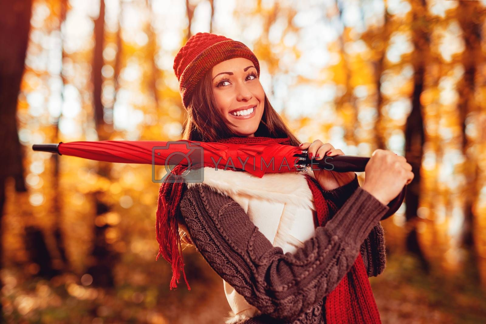 Portrait of a beautiful smiling girl with red umbrella in sunny forest in autumn colors. Pensive looking away.