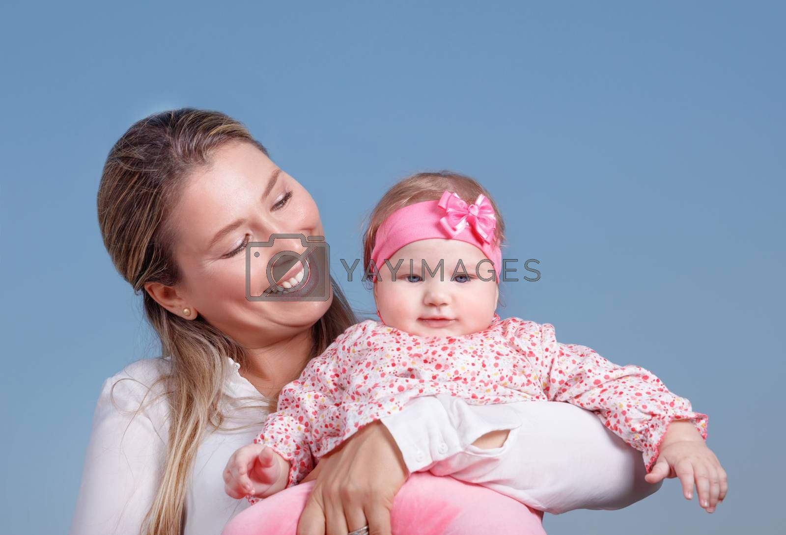 Portrait of happy cheerful mother holding on hand cute little daughter isolated on blue background, loving young family