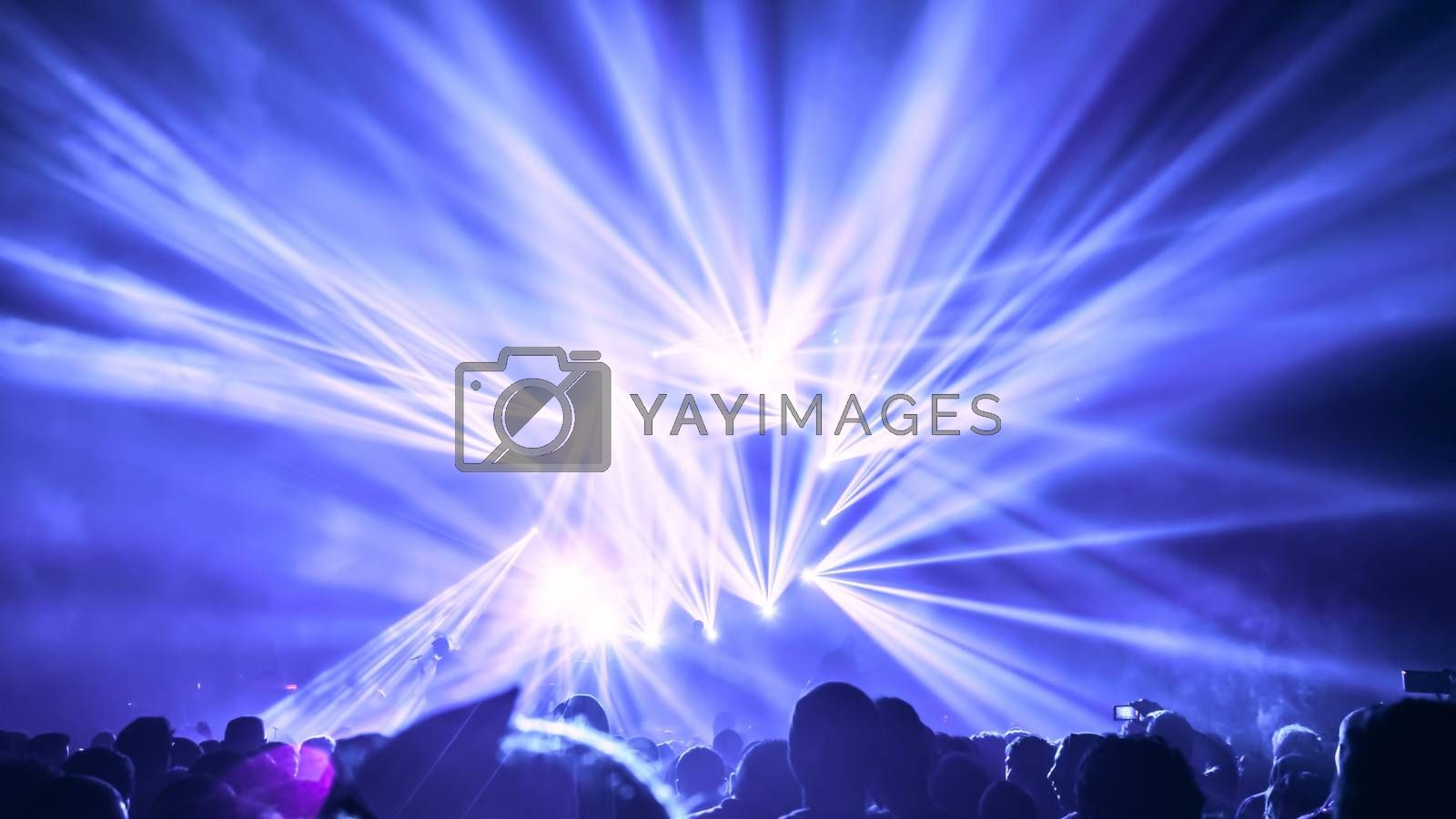 People on the party enjoying concert, dancing in the night club, celebrating new year eve, bright blue laser light background