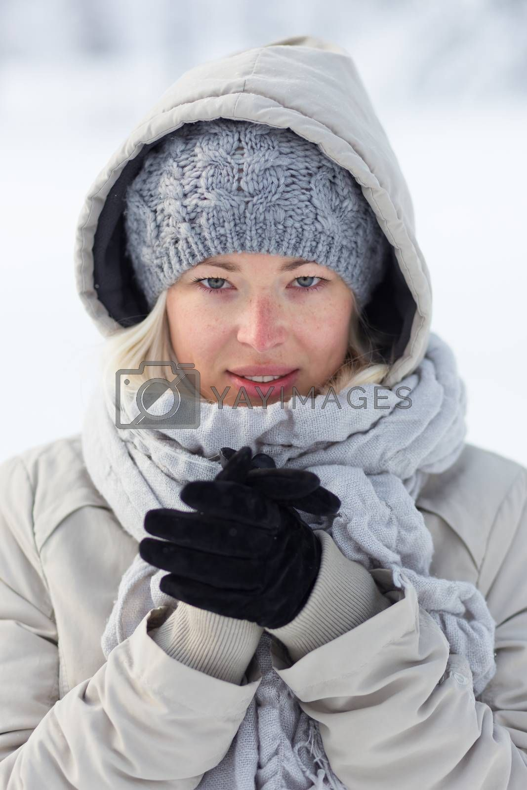 Portrait of cute casual young woman outdoor in snow in cold winter time.
