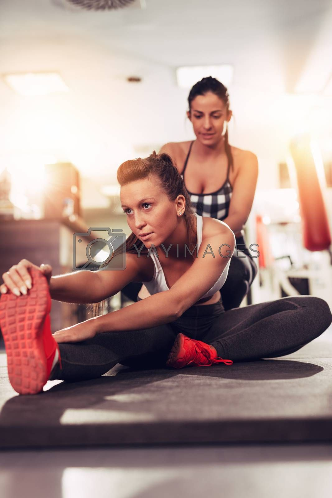 Beautiful young woman exercising at the gym with a female personal trainer.