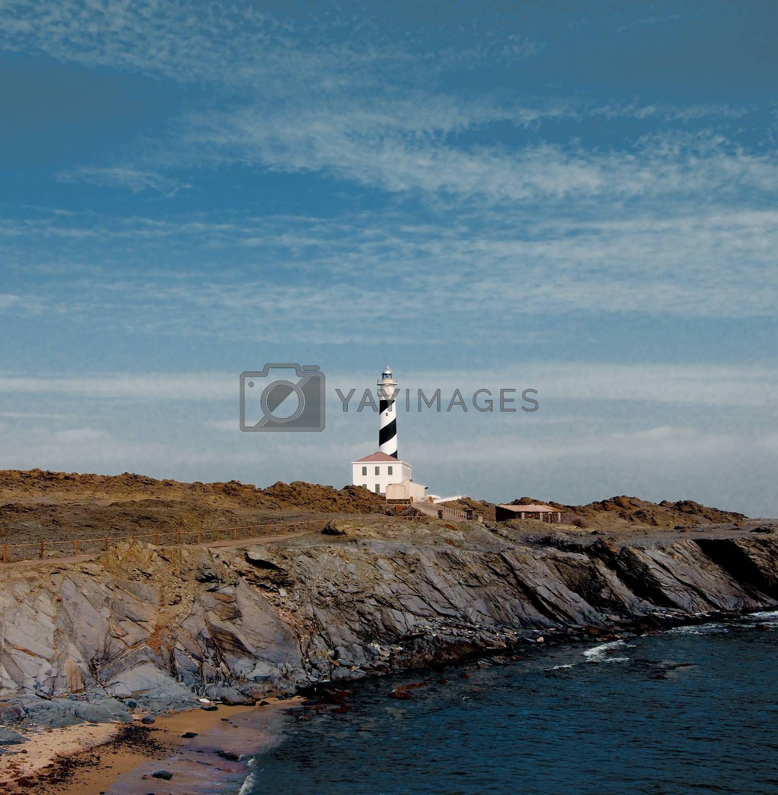 Lighthouse Faro de Favaritx against Dramatic Sky background. Menorca, Balearic Islands.