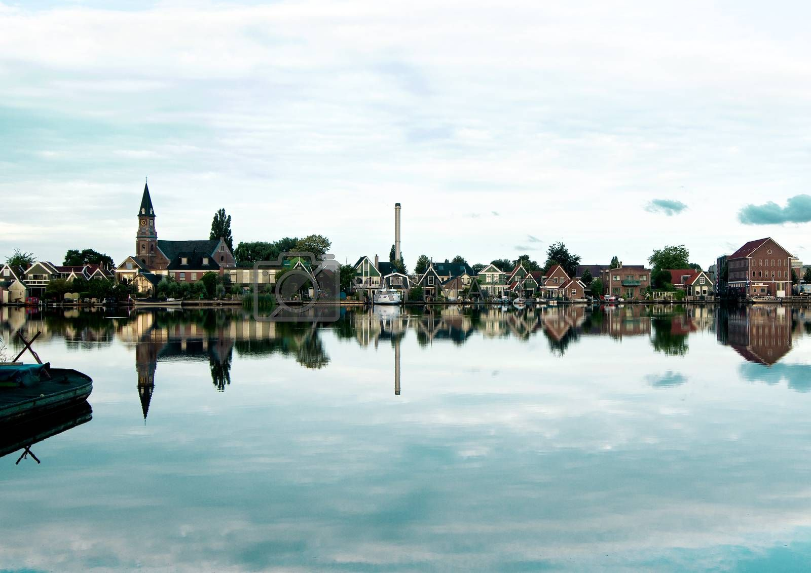 Houses and Church of Zaanse Schans on River Coast with Reflection Early Morning Outdoors. Netherlands