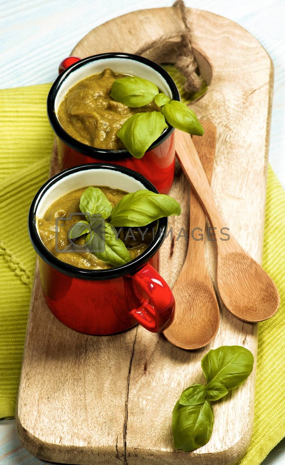 Delicious Vegan Cream Soup in Soup Cups with Wooden Spoons with Basil on Serving Board closeup on Wooden background