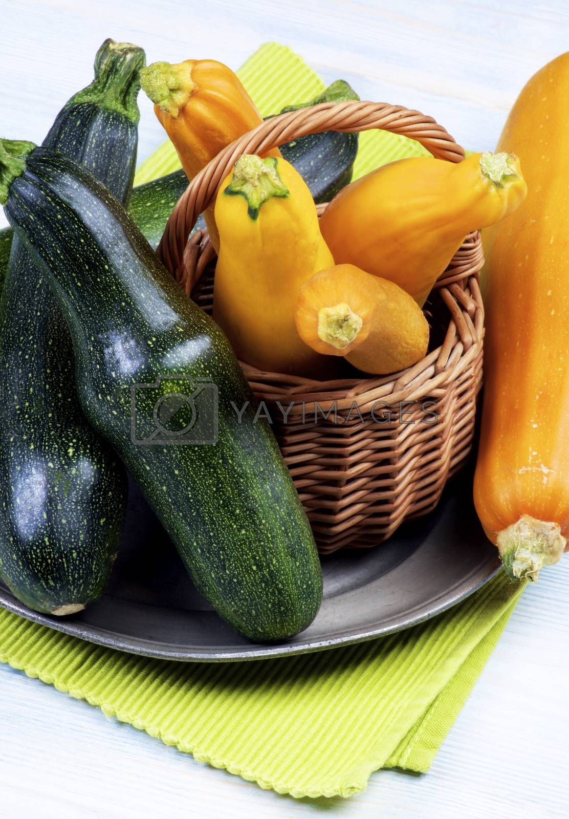 Arrangement of Green and Yellow Fresh Ripe Zucchini in Wicker Basket on Tin Plate closeup on Wooden background
