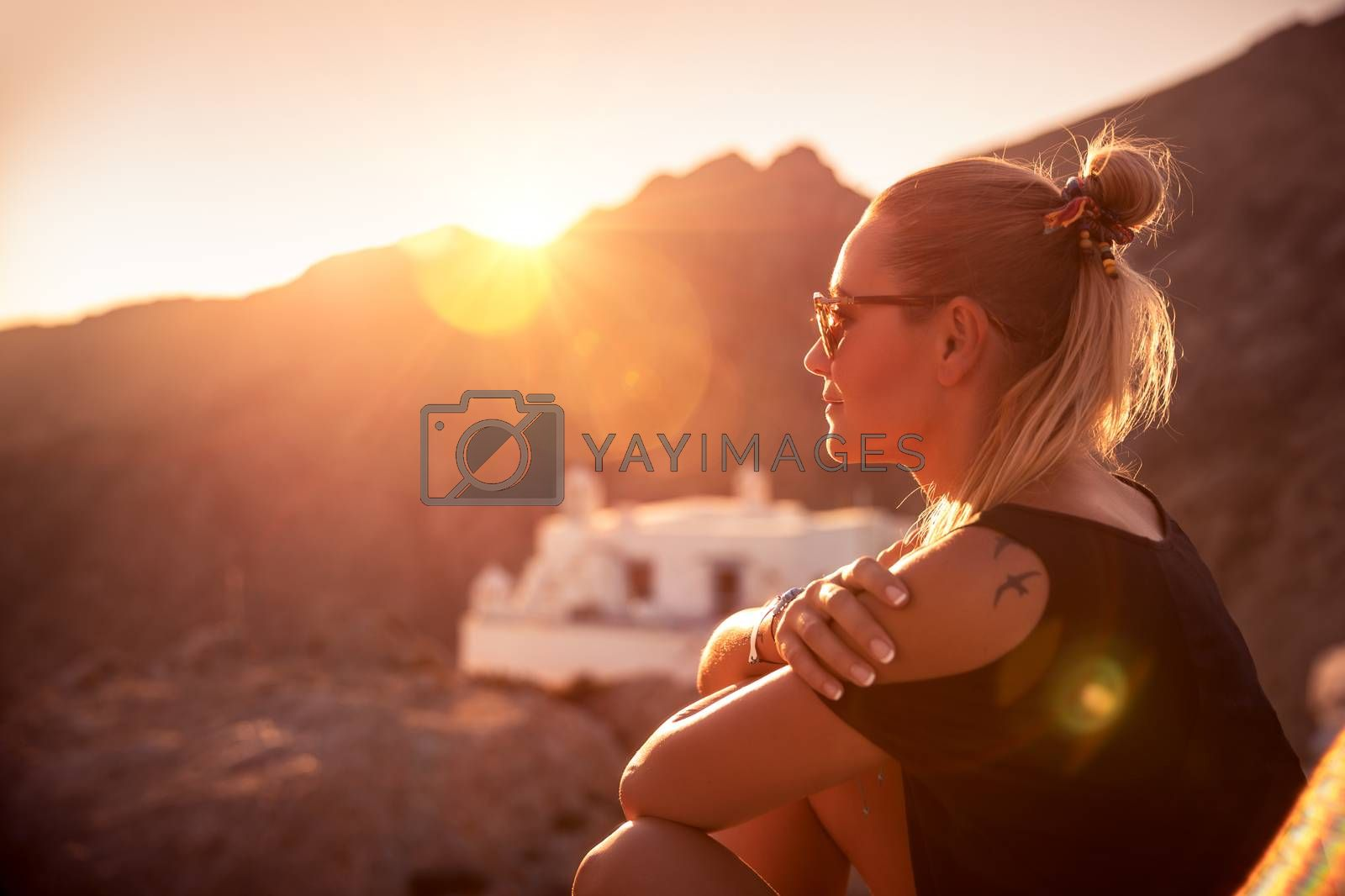 Beautiful woman enjoying travel, wonderful place on sunset light, girl sitting on the mountains near the monastery, happy summer holidays
