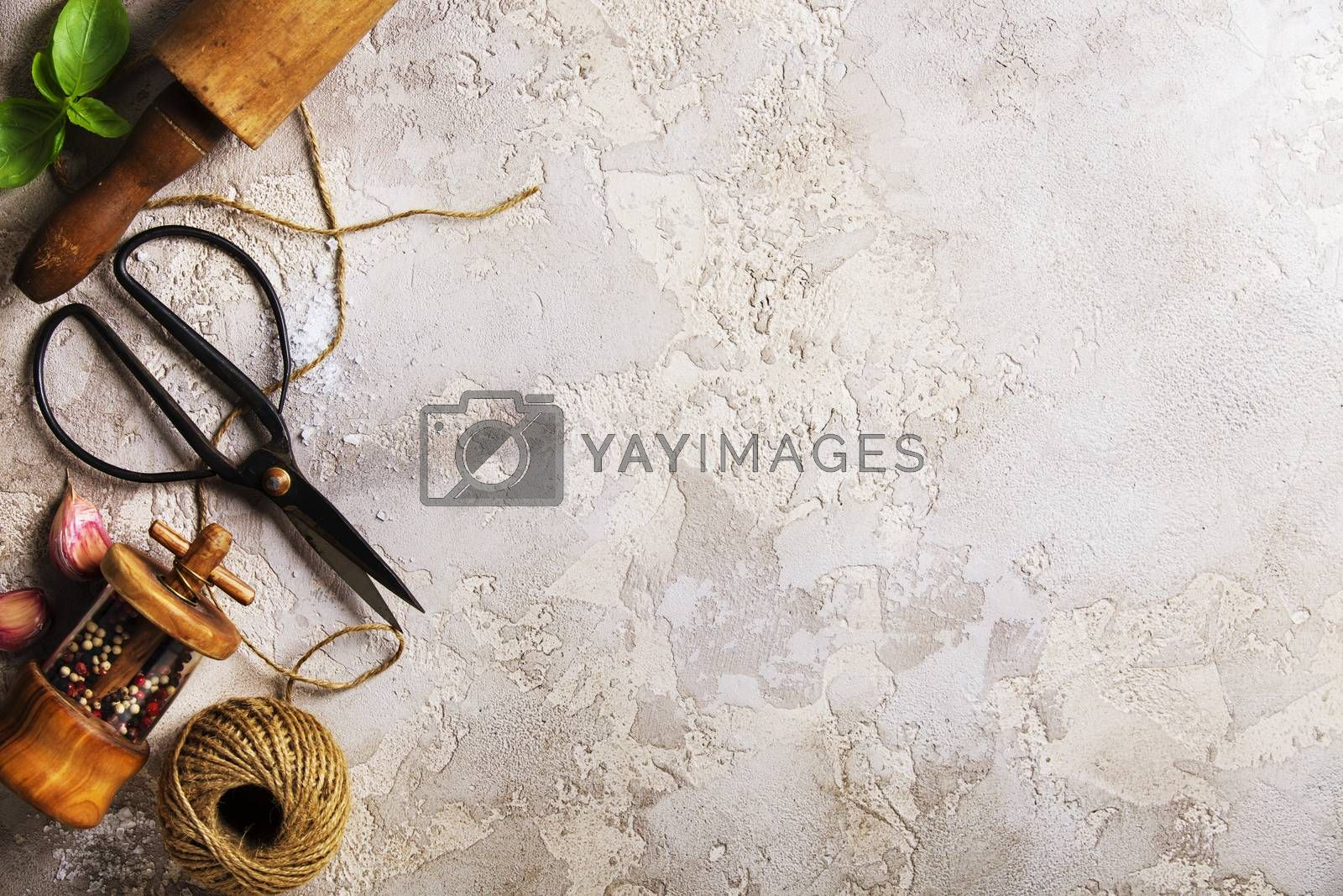 Cooking background: rolling pin, scissors, pepper, garlic and basil leaves. Cooking, healthy or traditional food concept. Home cooking utensils. Top view, copy space