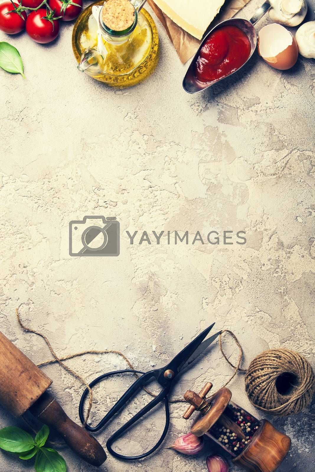 Cooking background: rolling pin, scissors, pepper, garlic, olive oil, eggs, cheese, tomato and basil leaves. Cooking, italian food  or vegetarian concept. Top view, copy space