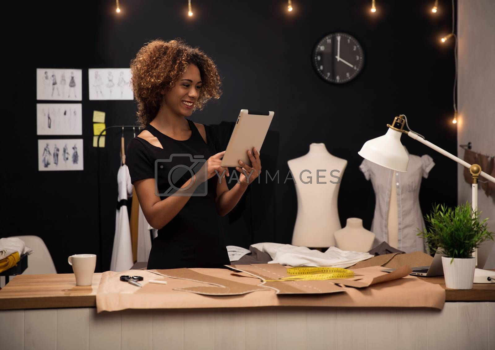 A young fashion designer on her atelier working with a tablet