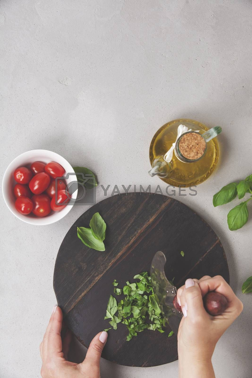 Hands of woman cooking italian food (tomato, basil, olive oil) on rustic background. Top view