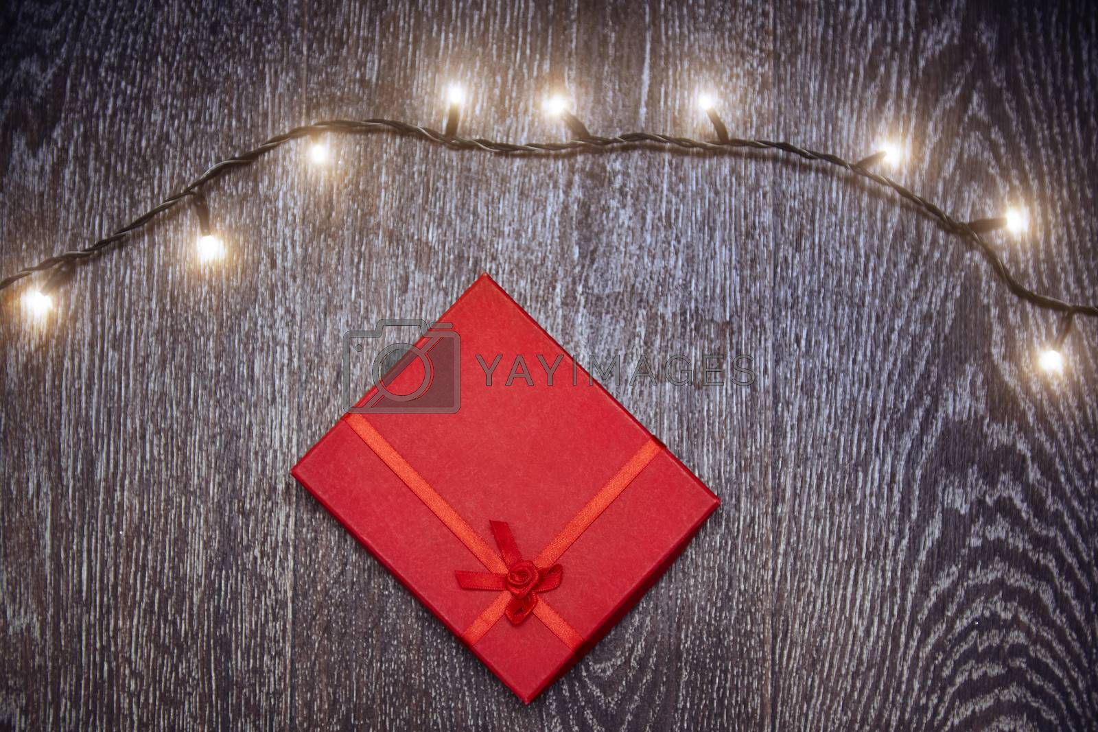 Christmas light and gift box on a hardwood background