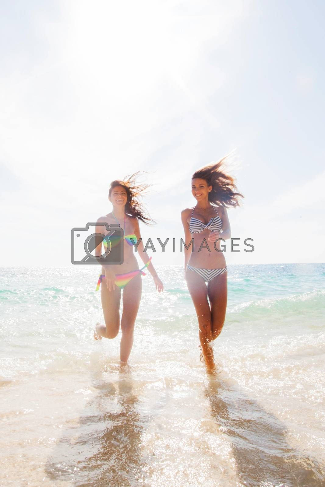 Two young and attractive women in bikini running by the beach