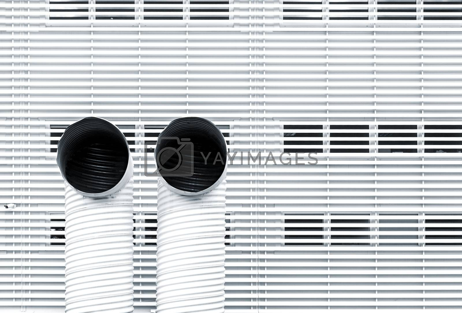 Abstract architecture picture with two ventilation pipes against striped metal facade