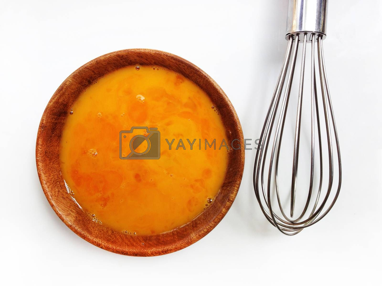 Fresh eggs in wooden bowl with egg whisk on white background by Bowonpat