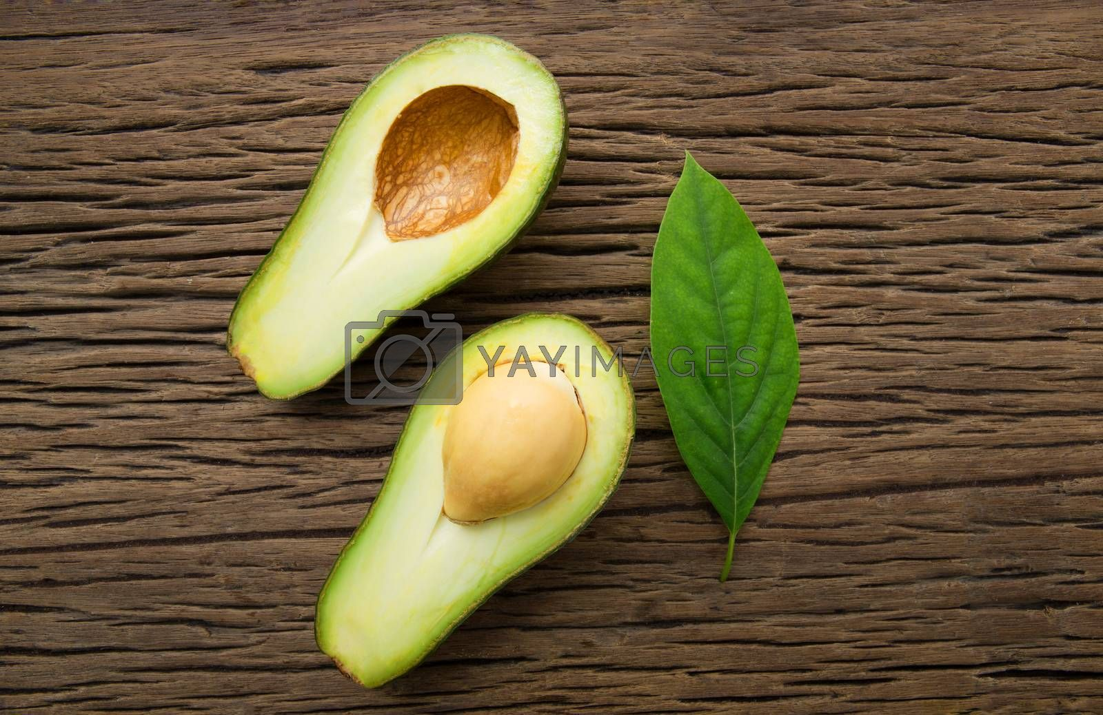 Avocado on a brown wood background. by Bowonpat