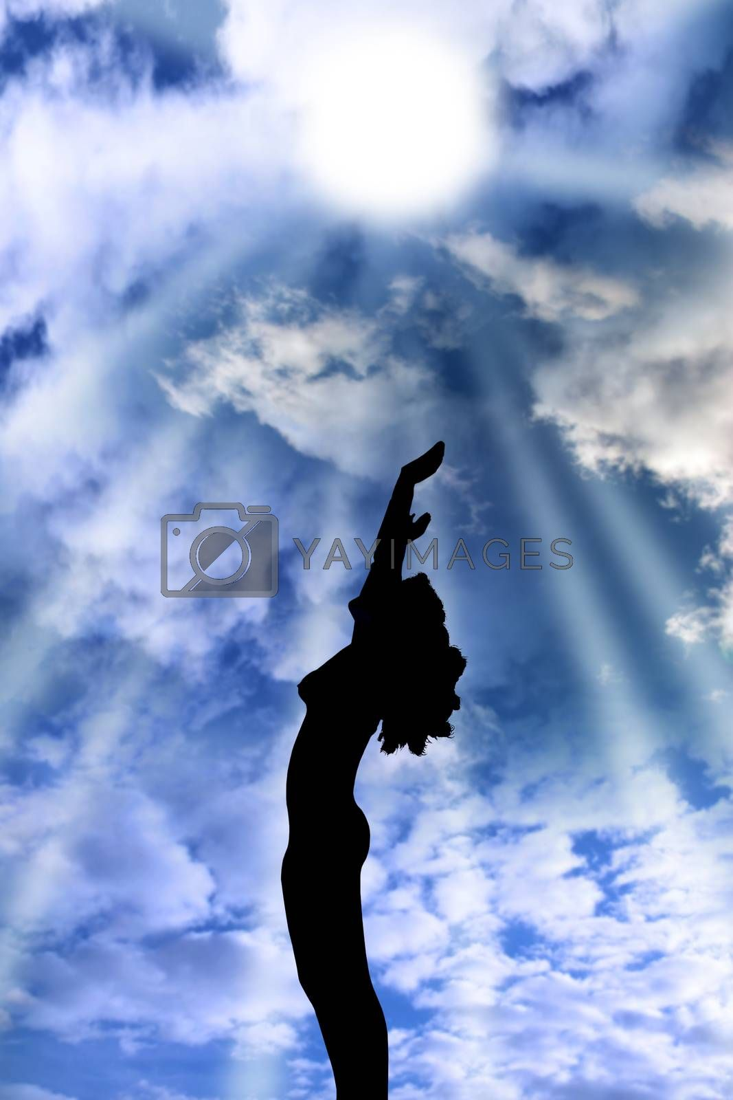 attractive silhouetted nude woman holding her hands up to the sky giving gratitude to the heavens in a yoga pose with a cloudy background