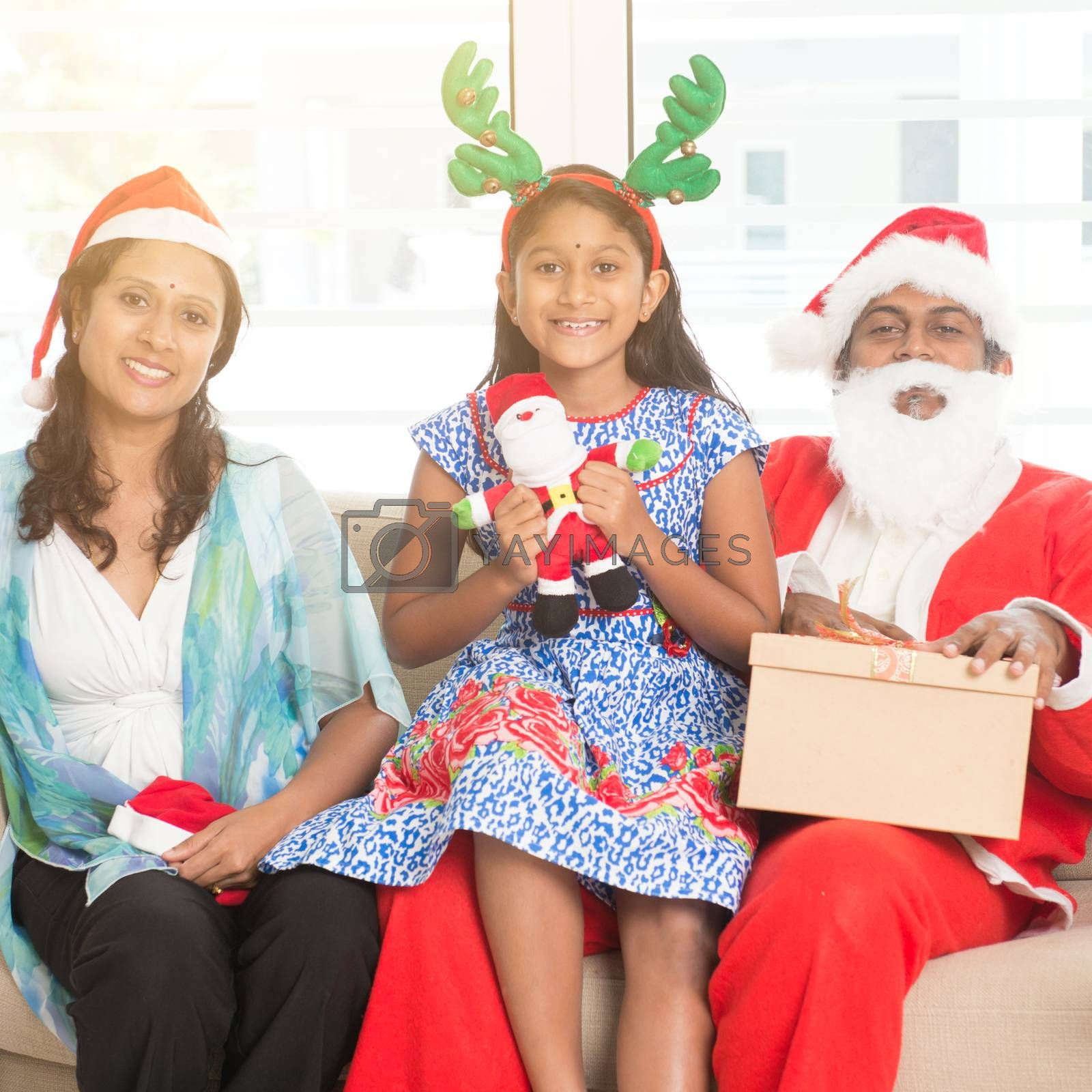 Happy Indian family celebrating Christmas holidays, with gift box and santa claus sitting on sofa at home, Asian people festival mood.