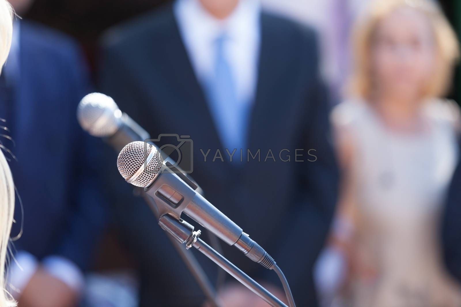 Press conference. Microphone in focus against blurred group of people.