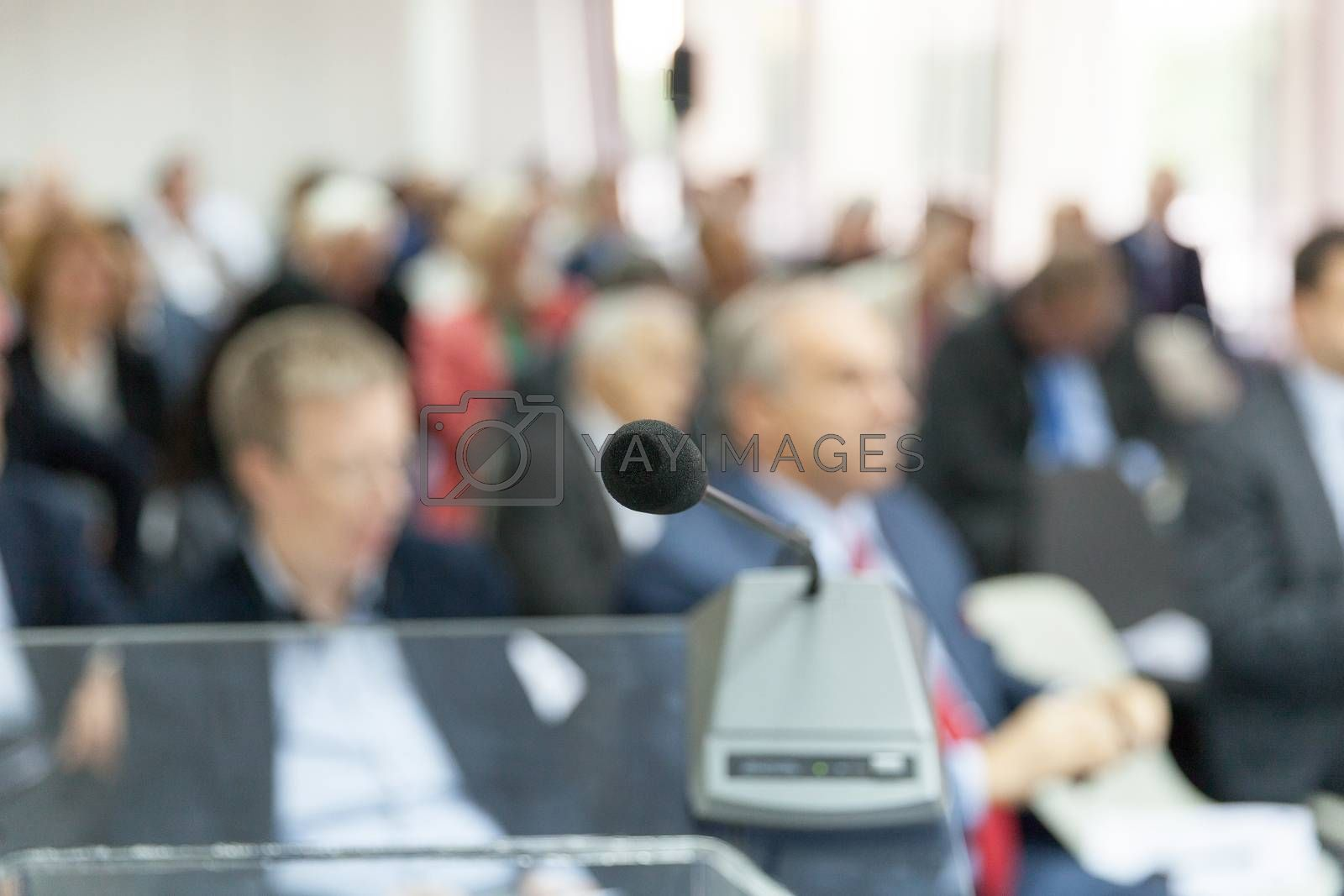 Microphone in focus against blurred audience. Participants at the professional or business conference.