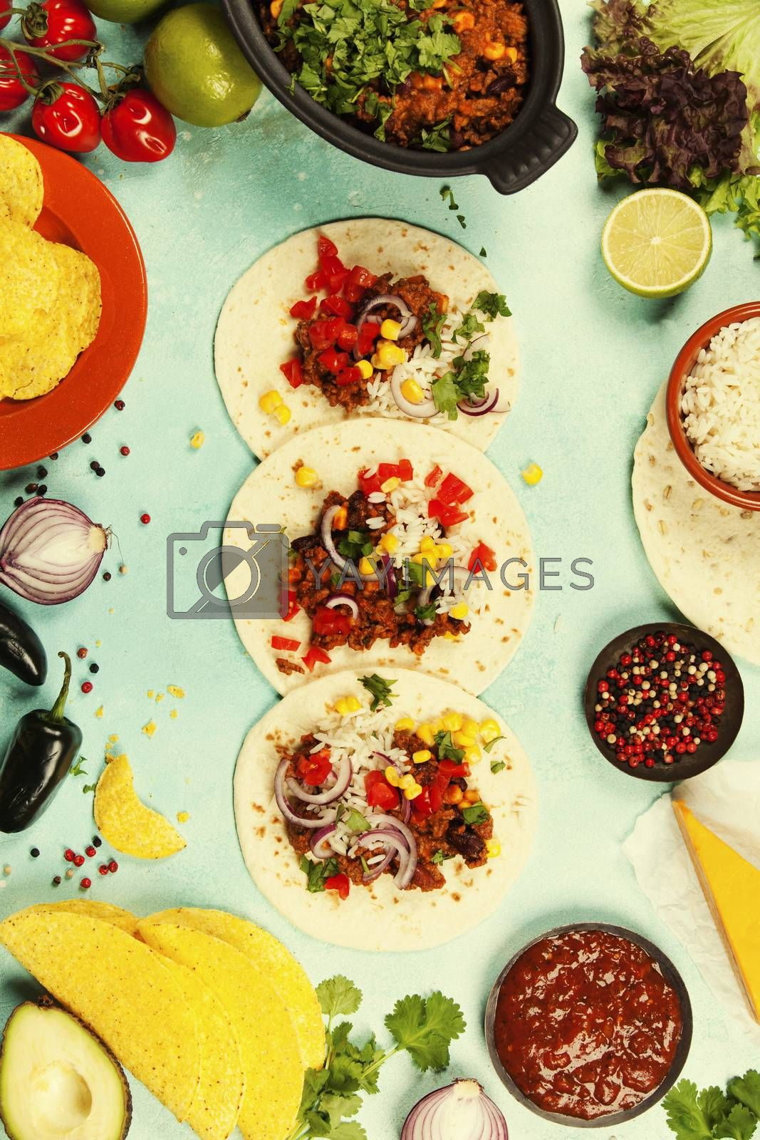 Mexican food concept: tortilla chips, guacamole, salsa, chili with beans and fresh ingredients over vintage background. Top view