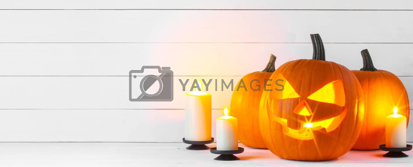 Halloween pumpkin head jack lantern and candles on white wooden background