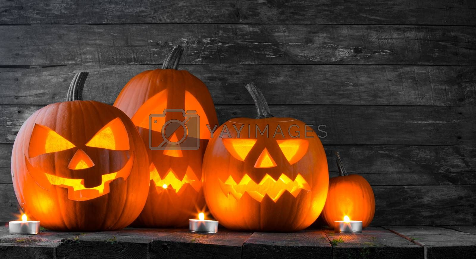 Halloween pumpkin heads jack o lantern and candles on wooden background