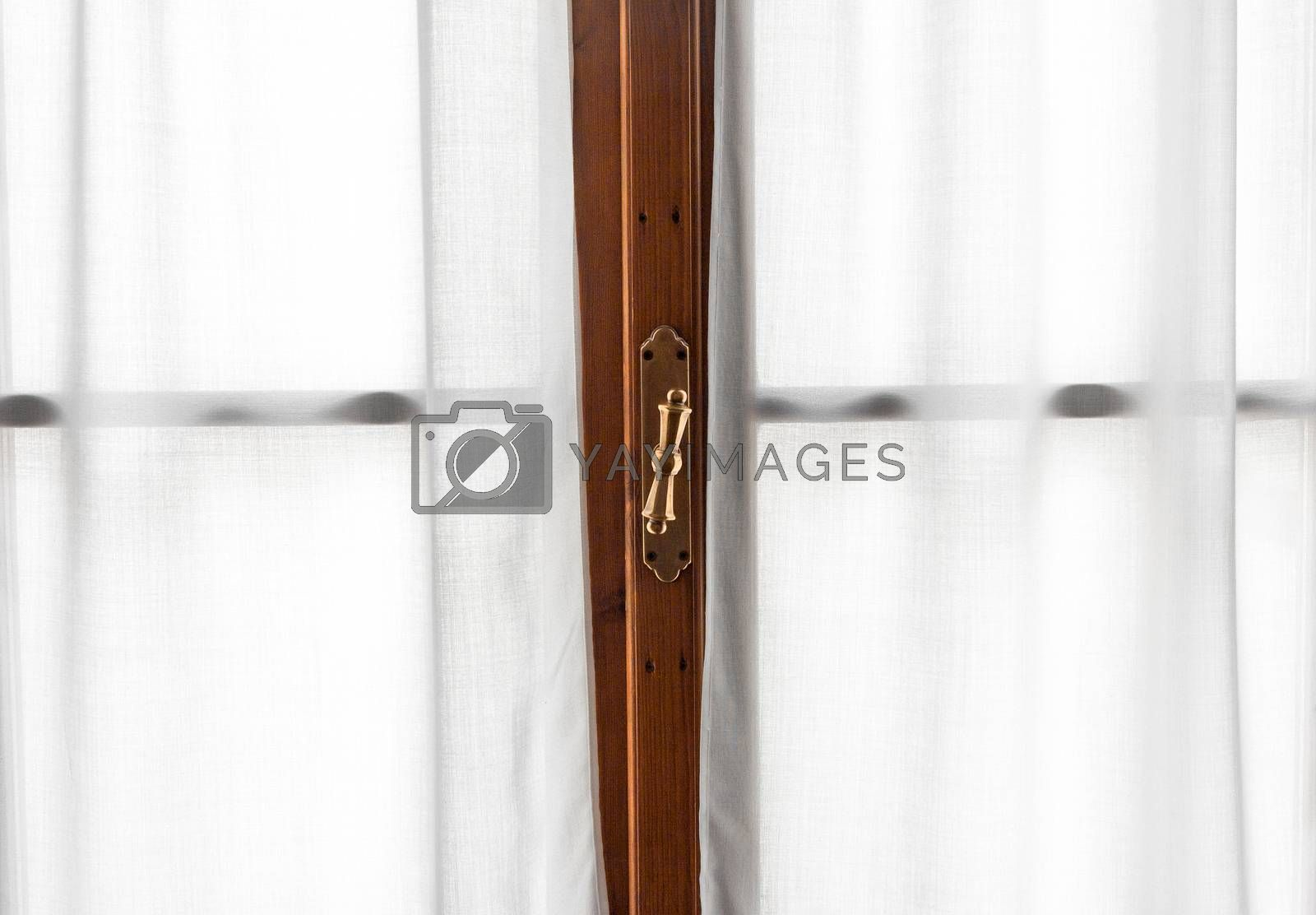 Window wooden frame detail with vintage shiny handle and white soft curtains