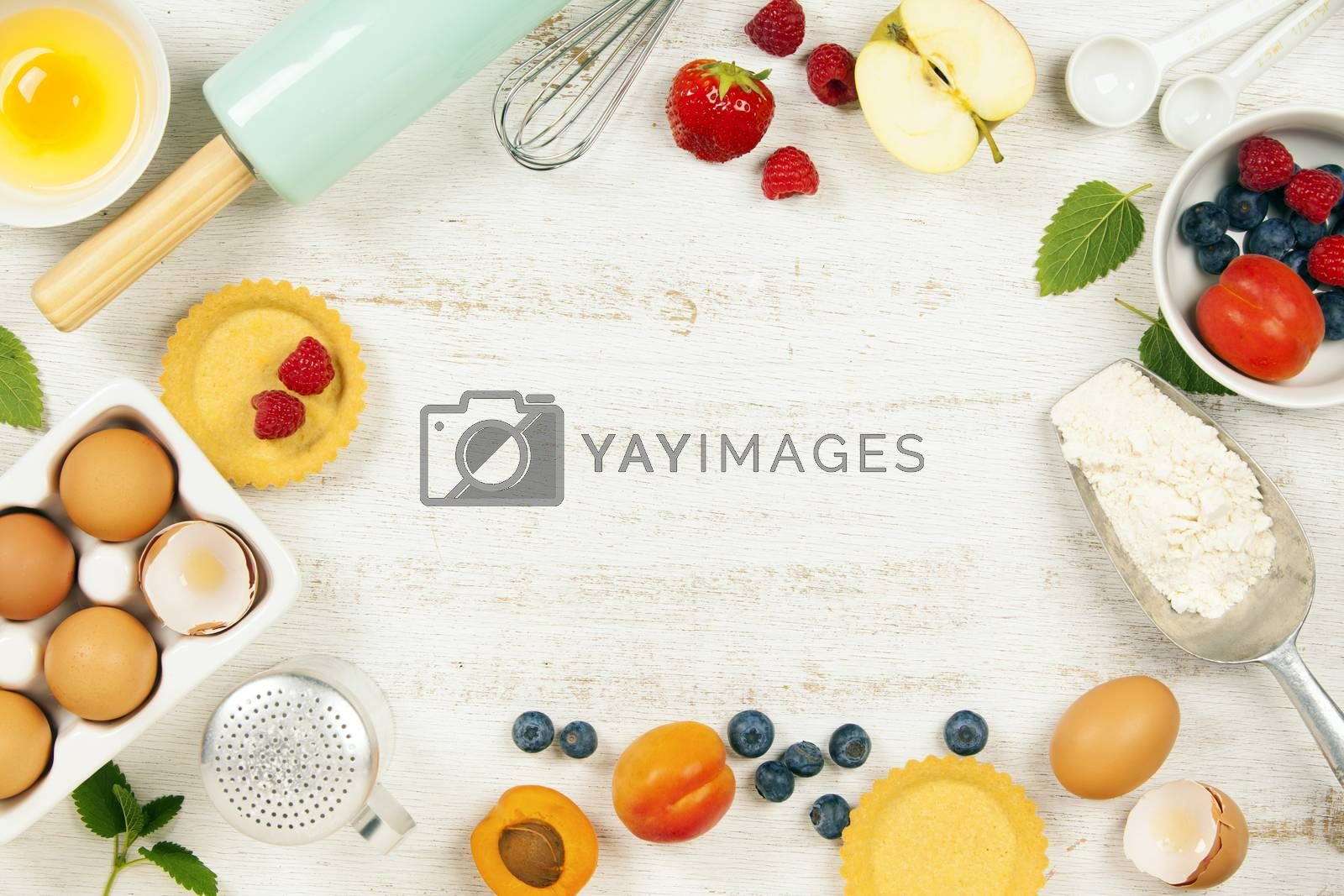 Baking tools and ingredients - flour, rolling pin, eggs, measuring spoons, fruits and berries on vintage wood table. Top view. Rustic background with free text space