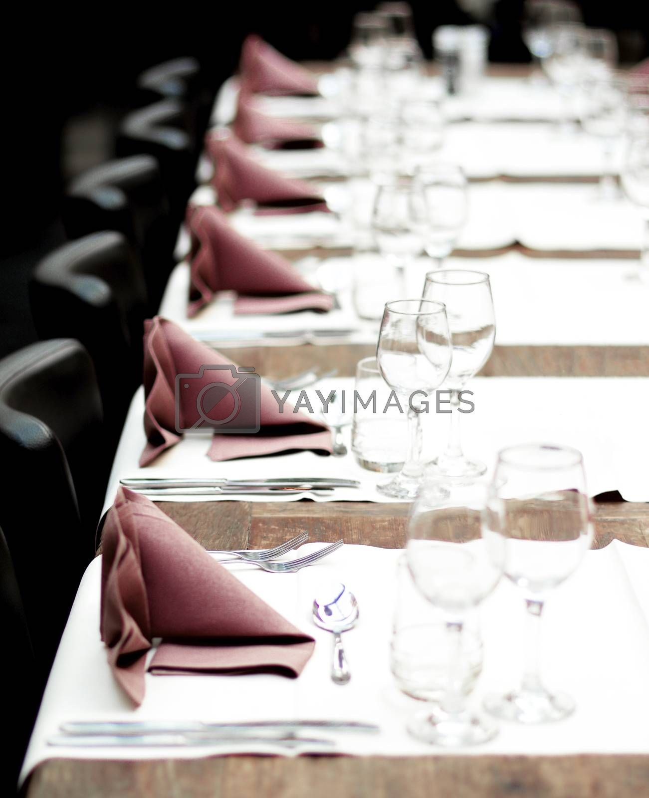 Restaurant Table Setting with Glasses, Silverware and Napkins on Vintage Wooden Table with Chairs closeup. Focus on Forks