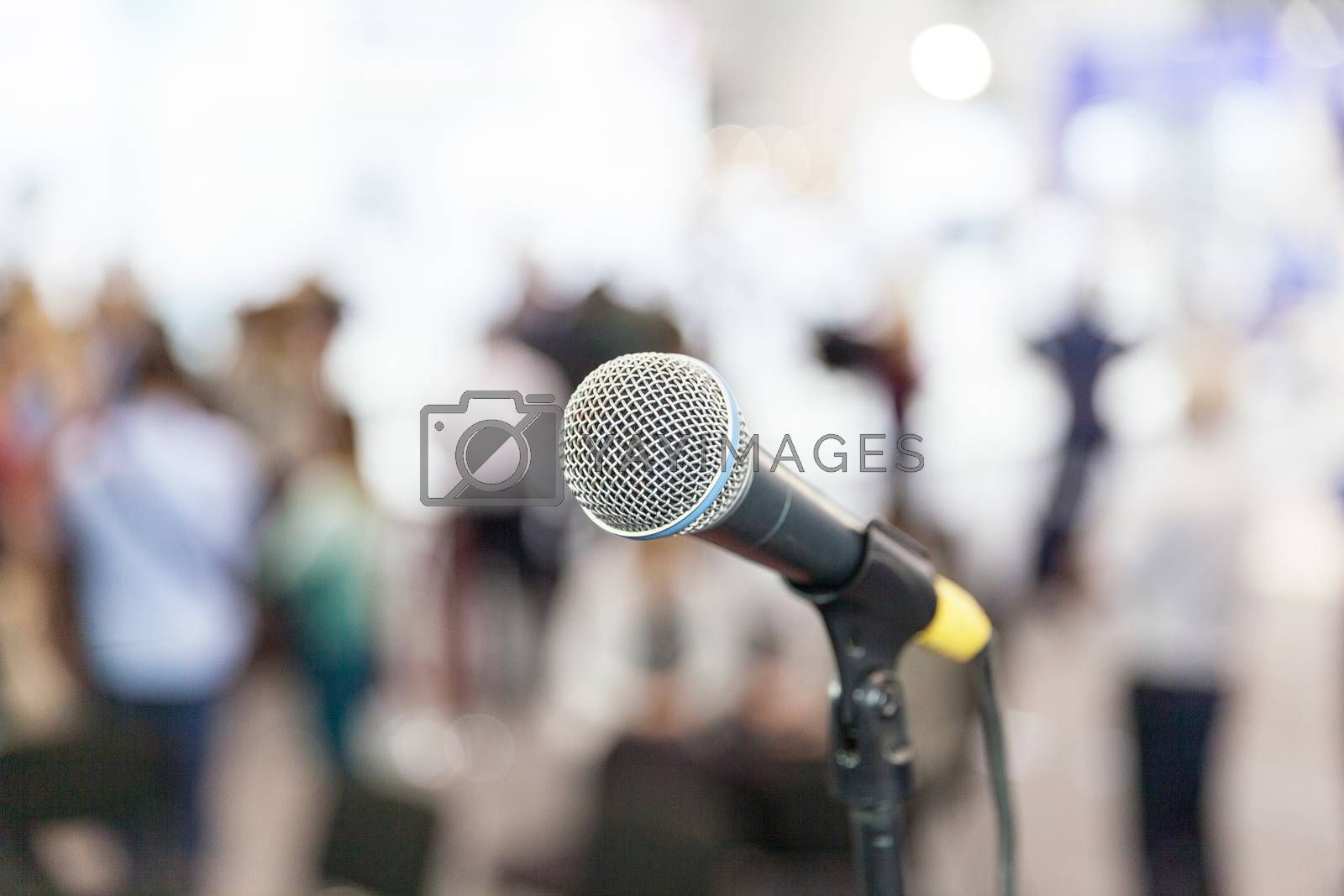 Microphone in focus against blurred people. News conference.